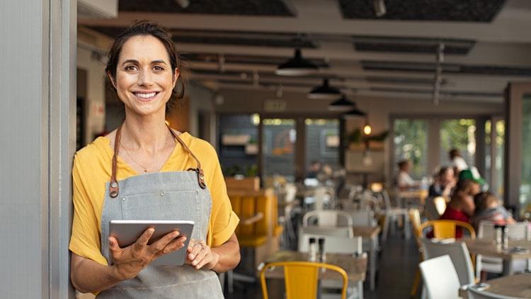 Frau steht mit Tablet vor ihrem Laden und lächelt